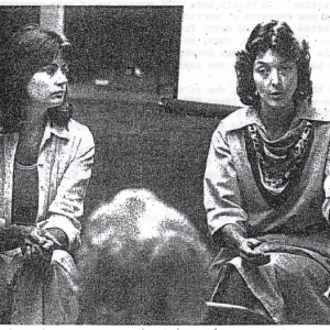 A black and white photo of two women talking to an audience.