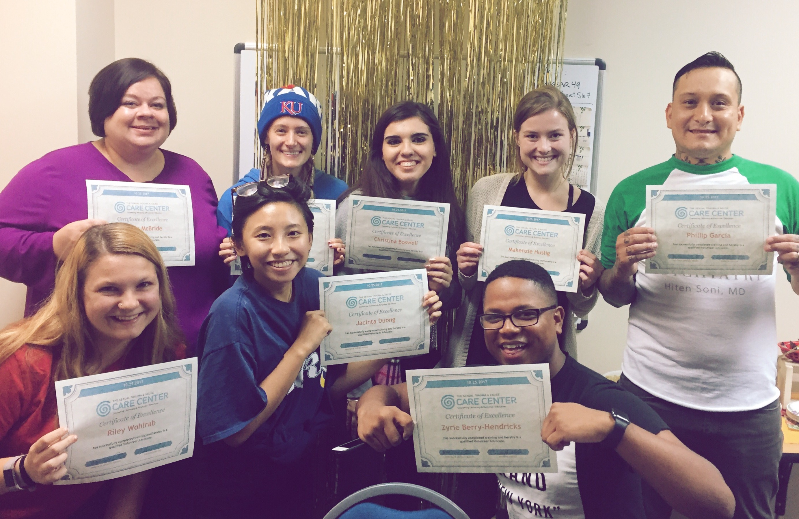 A group photo of Volunteer Advocates holding up certificates after finishing the Fall 2017 training.